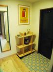 圧迫感があった玄関収納は撤去され、代わりにシンプルな木製のオープンラックを。...