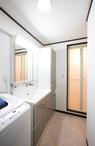 ホワイトの洗面台を採用して空間に明るさをもたらし、床はテーマカラーの薄いピン...