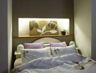 主寝室の壁はクロスの色を変えた棚を設けました。間接照明が優しい雰囲気の枕元に...
