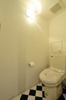 床材は洗面室と同じチェッカー柄。ペーパーホルダーやタオルリングも合わせて統一...
