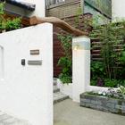 古木のアーチと真鍮製ライトが印象的な門