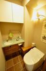 差し色のグリーンを利かせたモザイクタイルが可愛い手洗いカウンターを造作。床は...