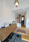 既設のドアや土間のタイルを活かすことでコストを抑えた玄関。部屋の雰囲気と調和...
