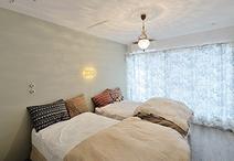 クローゼットは壁一面、天井までの引き戸にして大容量に。反面はベッドのヘッドボ...