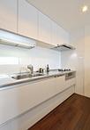 システムキッチンは部屋の色調に合わせてホワイトのラクエラ(クリナップ)を設置...