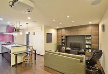 テレビボードが一体化した壁面収納は、全体の雰囲気に合わせて重厚感のある木目が...