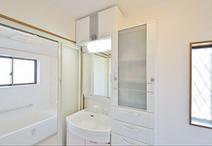 収納不足だった洗面室は、化粧台の隣に天井までのトール収納を配し、上部には換気...
