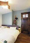 寝室は輸入ドアに合わせて一面をブルーグレーのクロスでアクセントに。リフォーム...