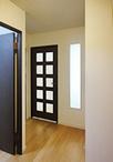 床はカーペットからフローリングに。リビングとの壁に明り取り窓を設け、玄関に光...