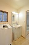階段の登り口とトイレの場所を移動することで、スペースが広がった洗面室。化粧台...