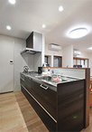 キッチンは、明るい内装のアクセントにブラウンカラーのクリナップ(ラクエラ)を...