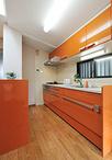 キッチンは「太陽のような温かみのあるものに」と奥様の好きなオレンジ色を採用。...
