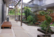 天然石を敷いて歩行性を確保したアプローチ。小さめのウッドデッキで、宅内からお...