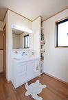 新しい洗面化粧台と洗濯機、タオルや掃除機を収納するスペース、サッシの前には室...