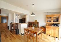 対面キッチンの向きを90度回転させ、垂壁を取り除くことで開放的になったダイニン...