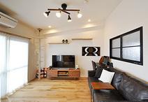 やさしい色味の壁・床・天井とブラックの室内窓・ソファー・照明のコントラストが...