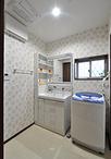 スペースを広げ収納付きの洗面化粧台(TOTO/サクア)と洗濯機を設置。入口は引き...