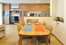 オープンキッチンの前にはダイニングスペースを配置。テーブルの高さに合わせてニ...