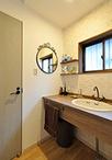 洗面は真鍮水栓を取付けレトロな雰囲気に。既設の窓枠に合わせて、木目調の洗面カ...