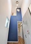 吹き抜けの高さが際立つ玄関ホール。正面の壁はネイビーブルーのクロスで印象度を...