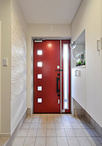 印象的なワインレッドの玄関ドアはLIXIL/ジエスタ。右には壁一面の玄関収納、向か...