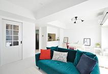 天井、壁、床が白で統一され、エメラルドグリーンのソファが目を引くリビング。ウ...
