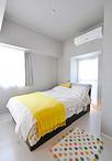 寝室は淡いグレーの壁紙にしてシックな内装に。ベッドはウォークスルークローゼッ...
