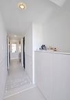 玄関収納や床をホワイトにし、既設の建具枠もホワイトにすることで清潔感ある白い...