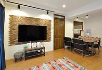 壁掛けテレビの背面は、凸凹のあるブラックウォールナットのウッドパネル(東亜通...