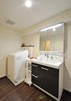 廊下との境には扉を設けず開放。洗面化粧台は梁の高さギリギリで設置可能だったLI...